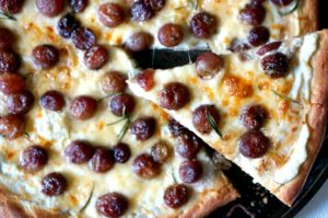 Roasted Grape Pizza may seem fancy (or weird).  But it's pizza, so it's not!  Bring the classic fruit and cheese combo to the supper table with our delicious and easy to make white pizza topped with ricotta and roasted grapes!